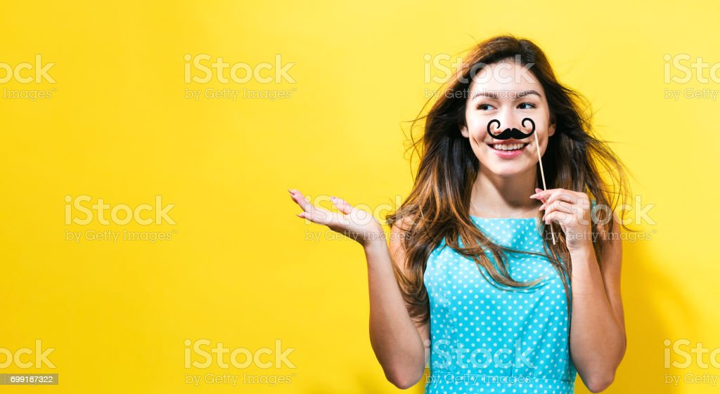 Young woman holding paper party sticks stock photo