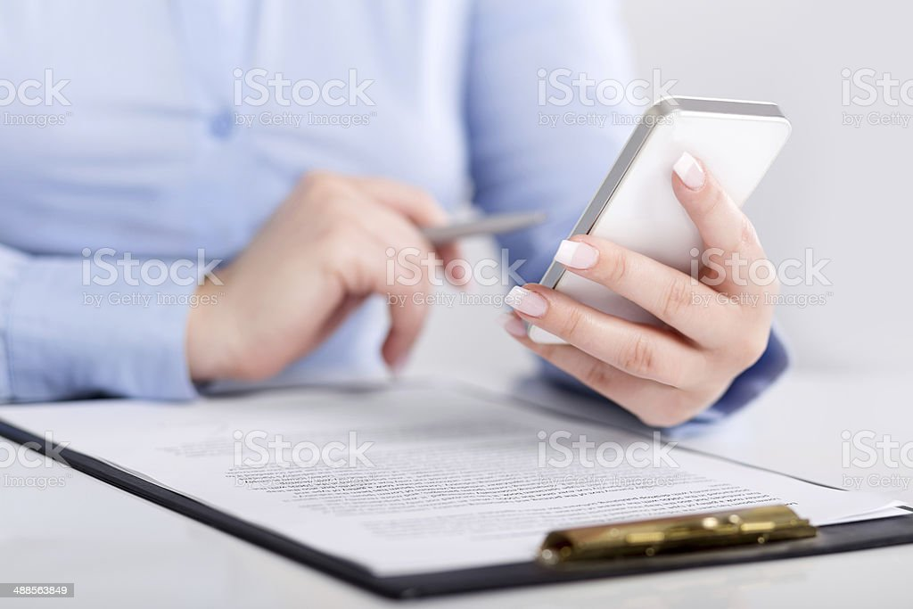 Young woman holding pen and using mobile phone royalty-free stock photo