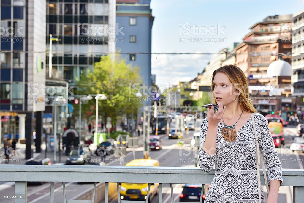 Young woman holding phone, central Stockholm stock photo