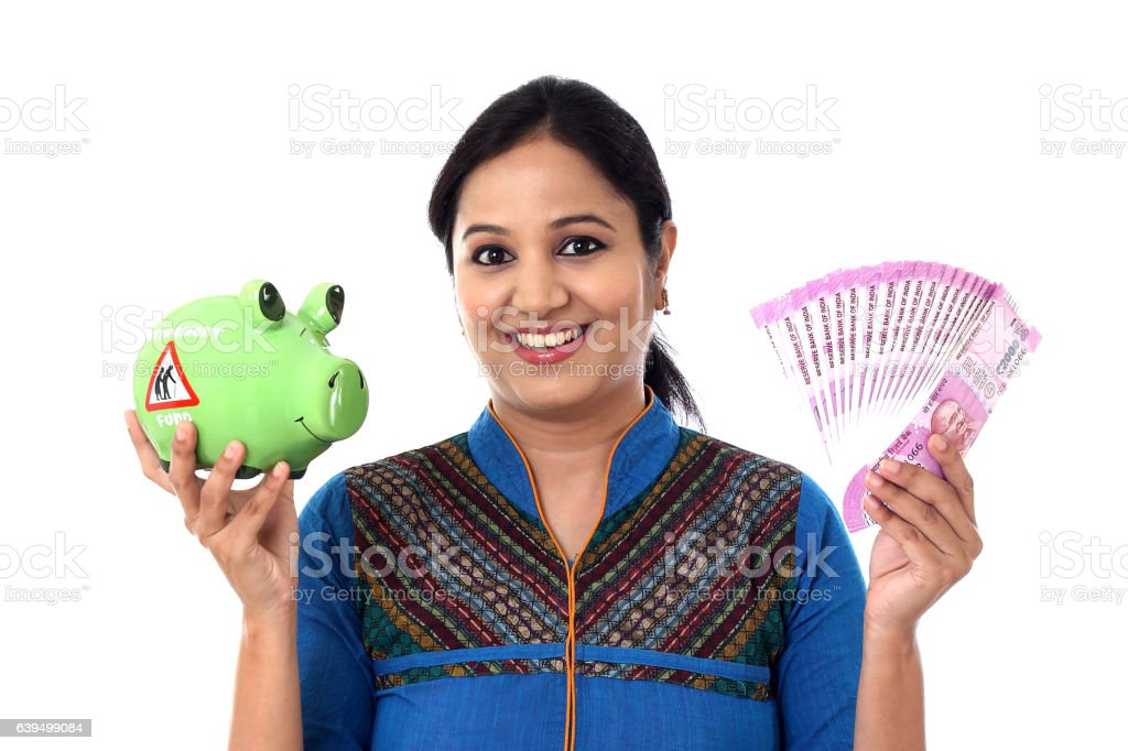 Young woman holding piggy bank and rupee notes-Money savings concept stock photo