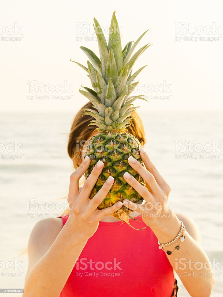 Young Woman Holding Pineapple On The Beach stock photo