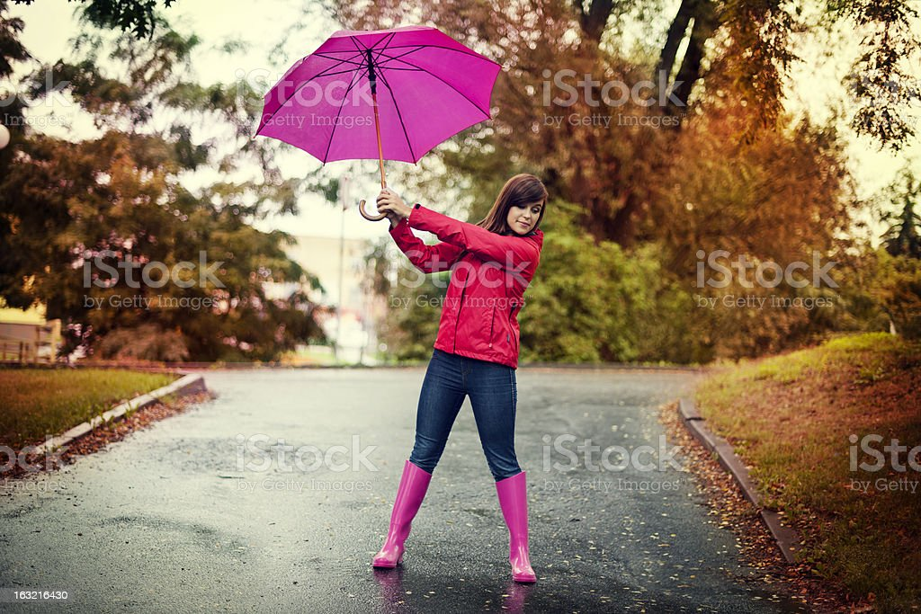 Young woman holding pink umbrella in a park stock photo