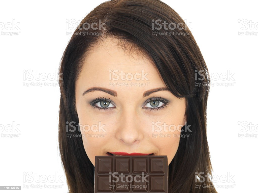 Young Woman Holding Plain Dark Chocolate Bar On Her Lips stock photo