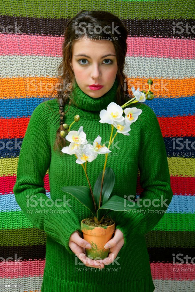 Young Woman Holding Pot of Orchid Flowers stock photo