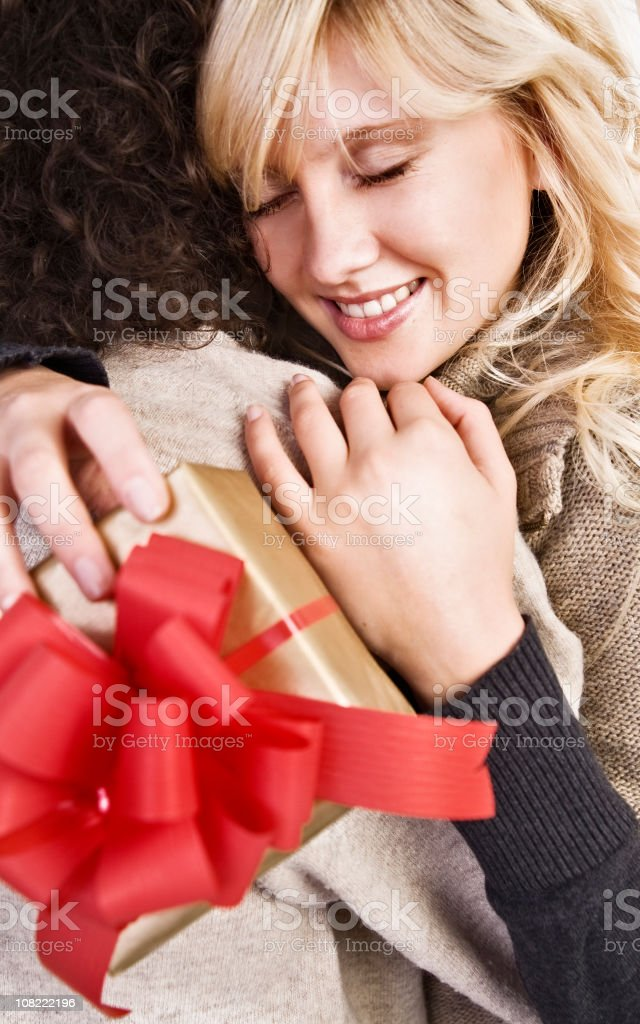 Young Woman Holding Present and Hugging Man royalty-free stock photo