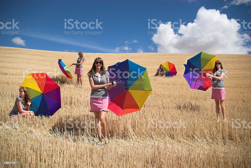 Young Woman Holding Rainbow Umbrella in Field, Various Poses royalty-free stock photo