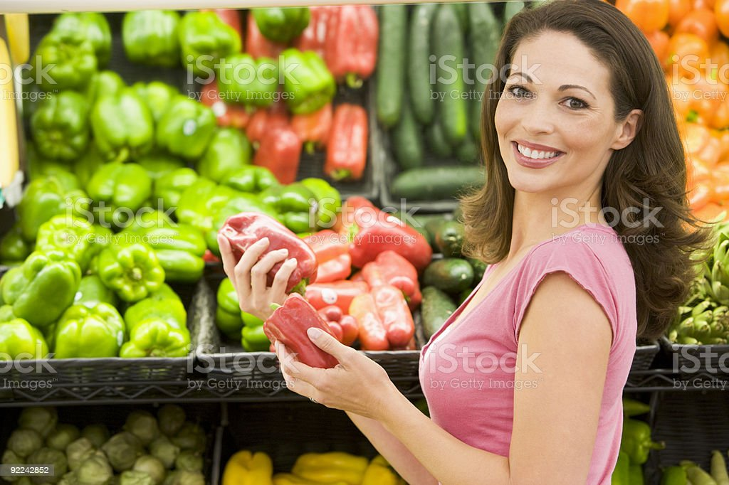 Young woman holding red capsicums in a grocery store royalty-free stock photo
