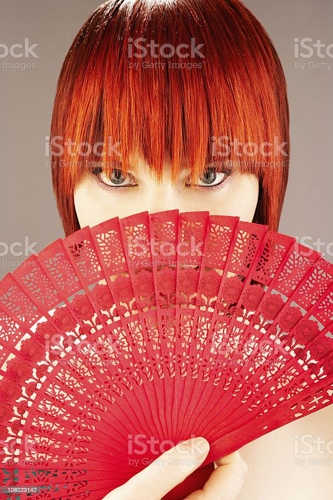 Young Woman Holding Red Japanese Fan in Front of Face royalty-free stock photo