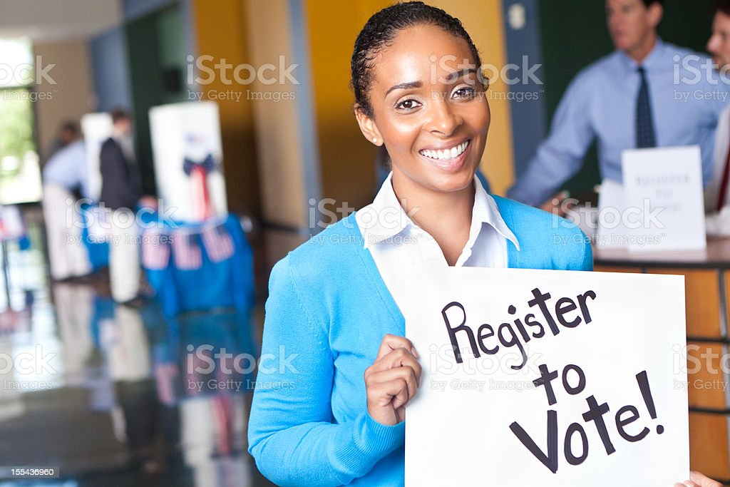 Young woman holding register to vote sign at voting center stock photo