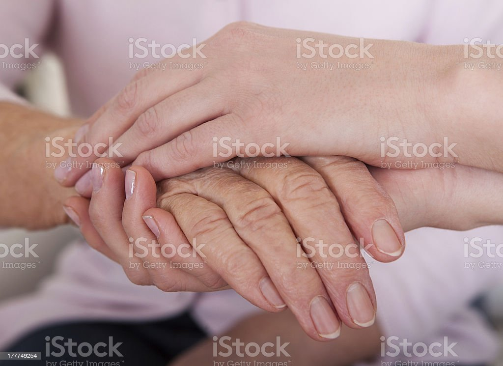 Young Woman Holding Senior Woman's Hand royalty-free stock photo
