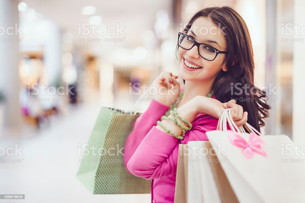 Young woman holding shopping bags in a shopping mall stock photo