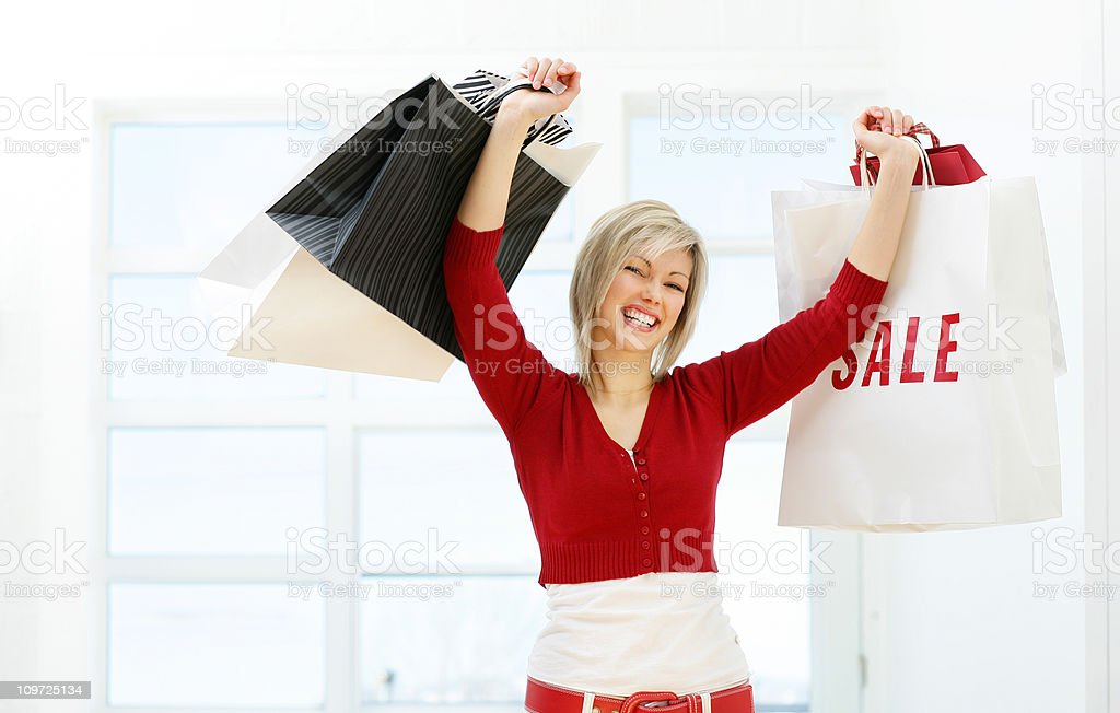 Young Woman Holding Shopping Bags Triumphantly royalty-free stock photo