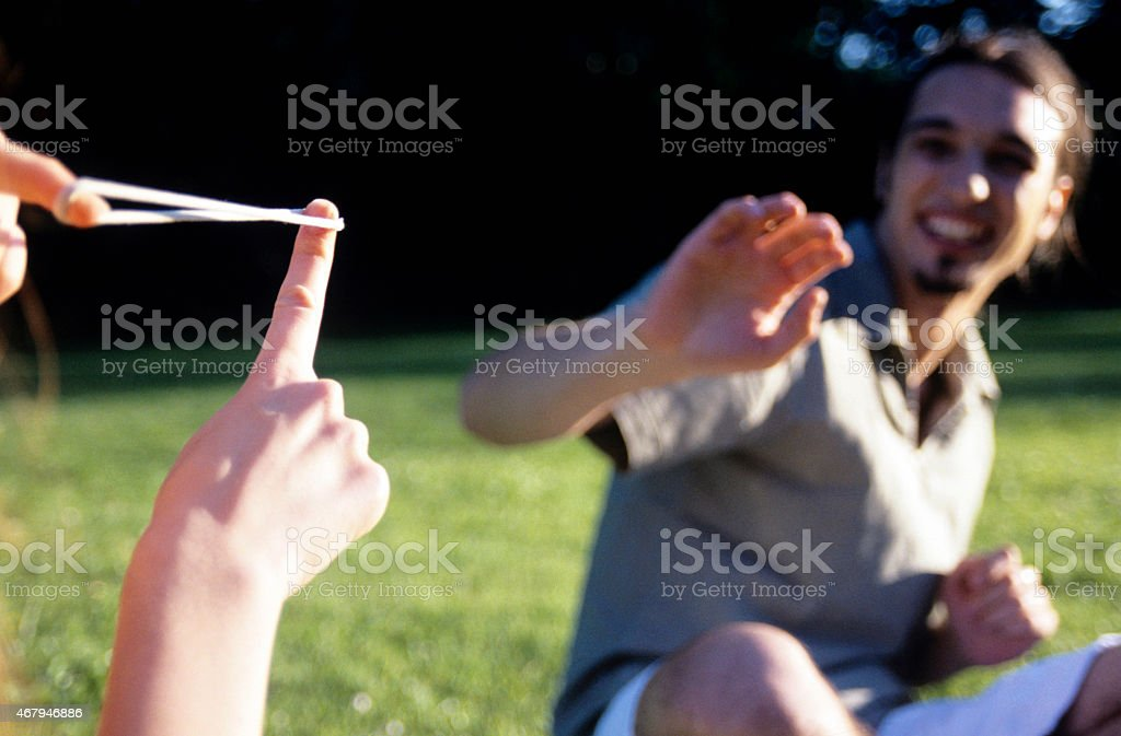 Young woman holding slingshot to young man in garden stock photo