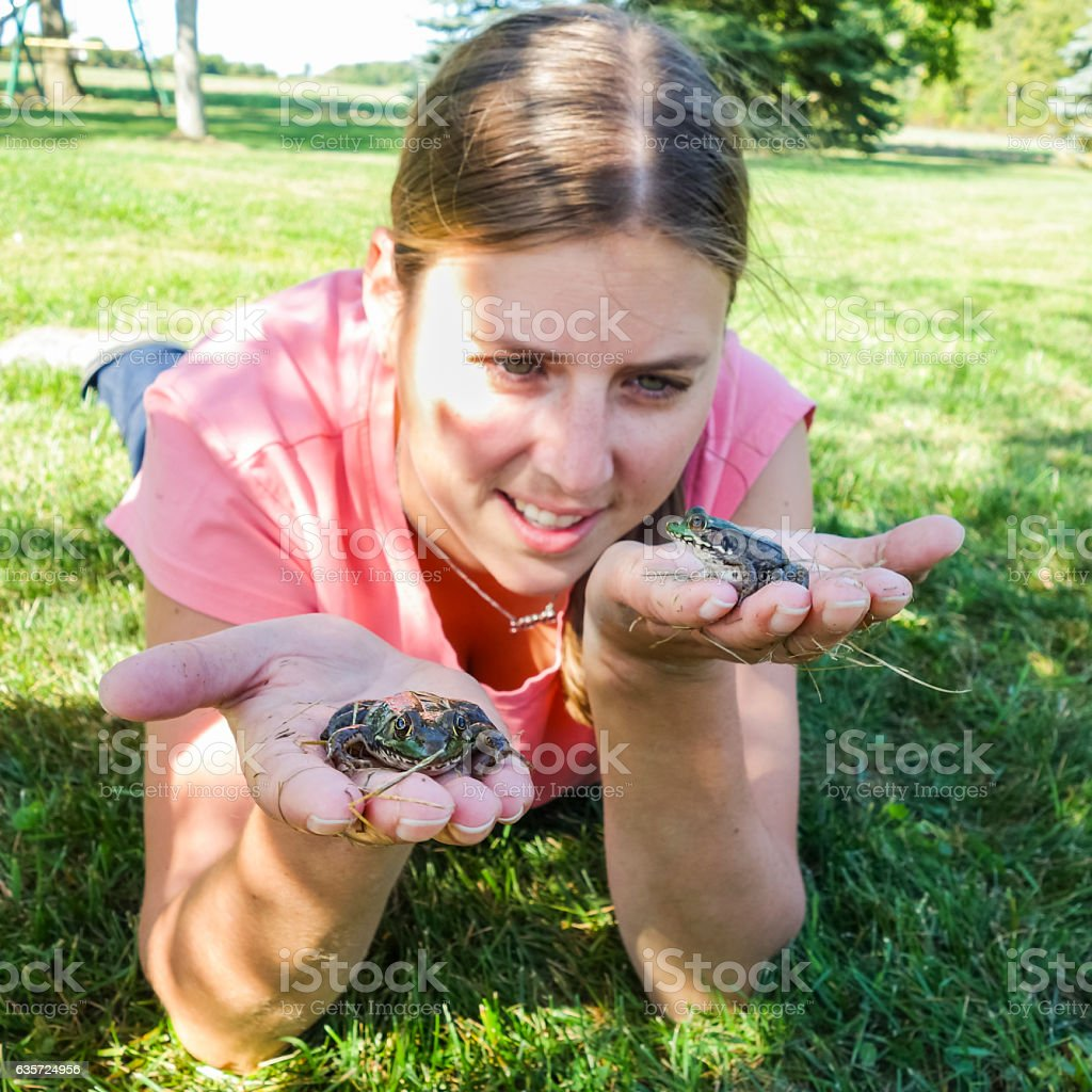 Young Woman Holding Two Frogs in her Hands Observing Differences stock photo