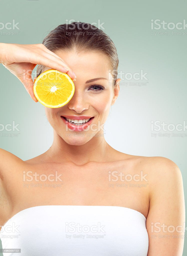 Young woman holding two orange halves against a green background stock photo