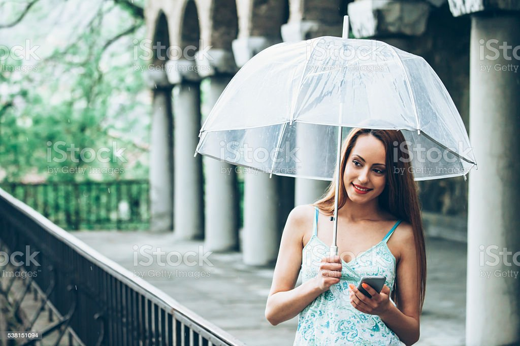 Young woman holding umbrella and using phone under the rain stock photo