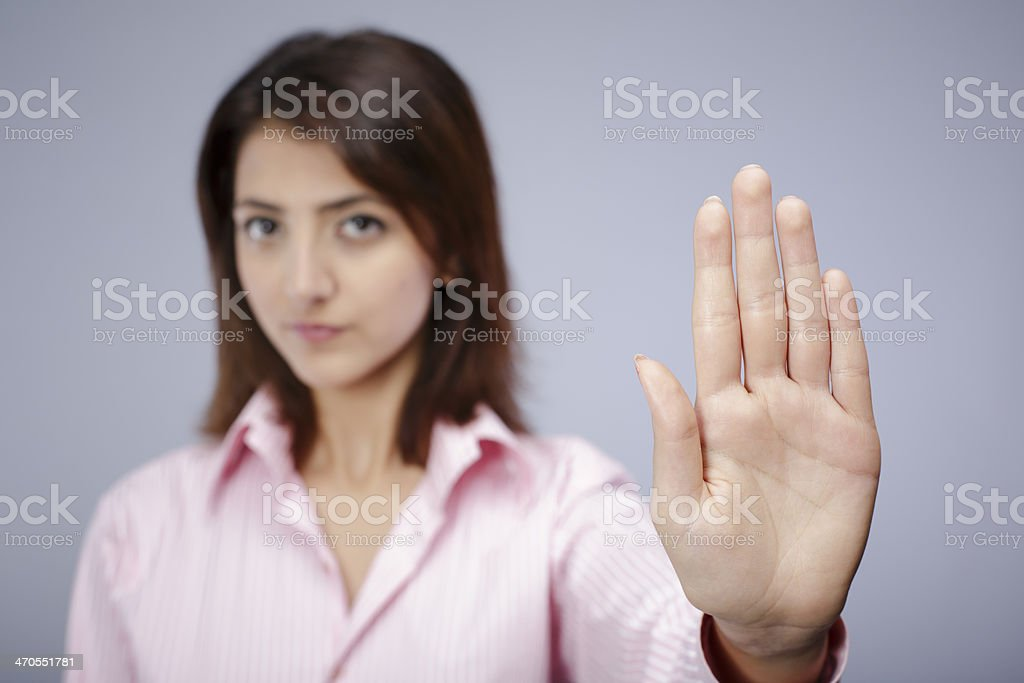 Young woman holding up her left hand to stop someone stock photo