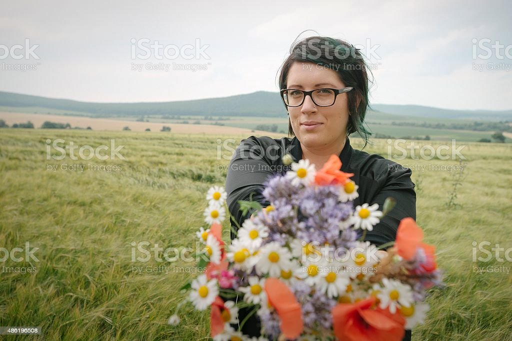 Young woman holding wild flowers bouquet and posing stock photo
