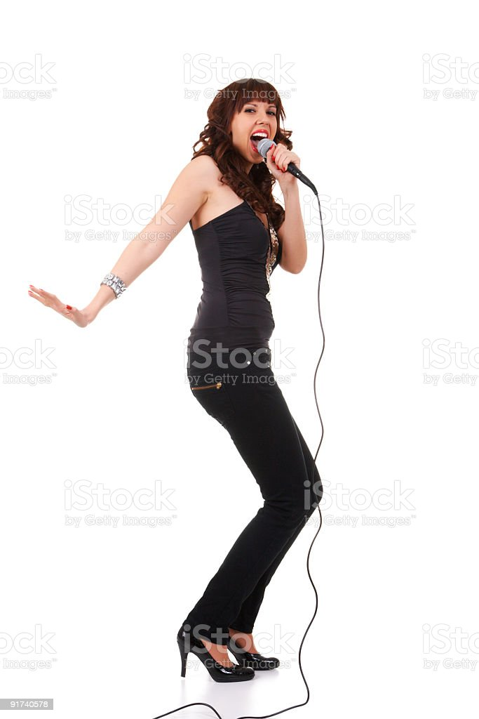 Young woman holding wired microphone and singing stock photo