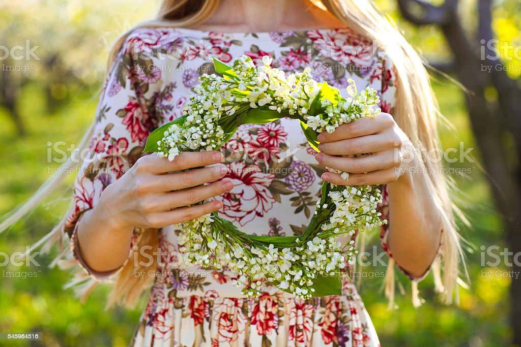 Young woman holding wreath from lily of the valley stock photo