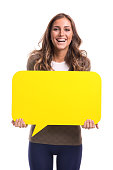 Young woman holding yellow speech bubble