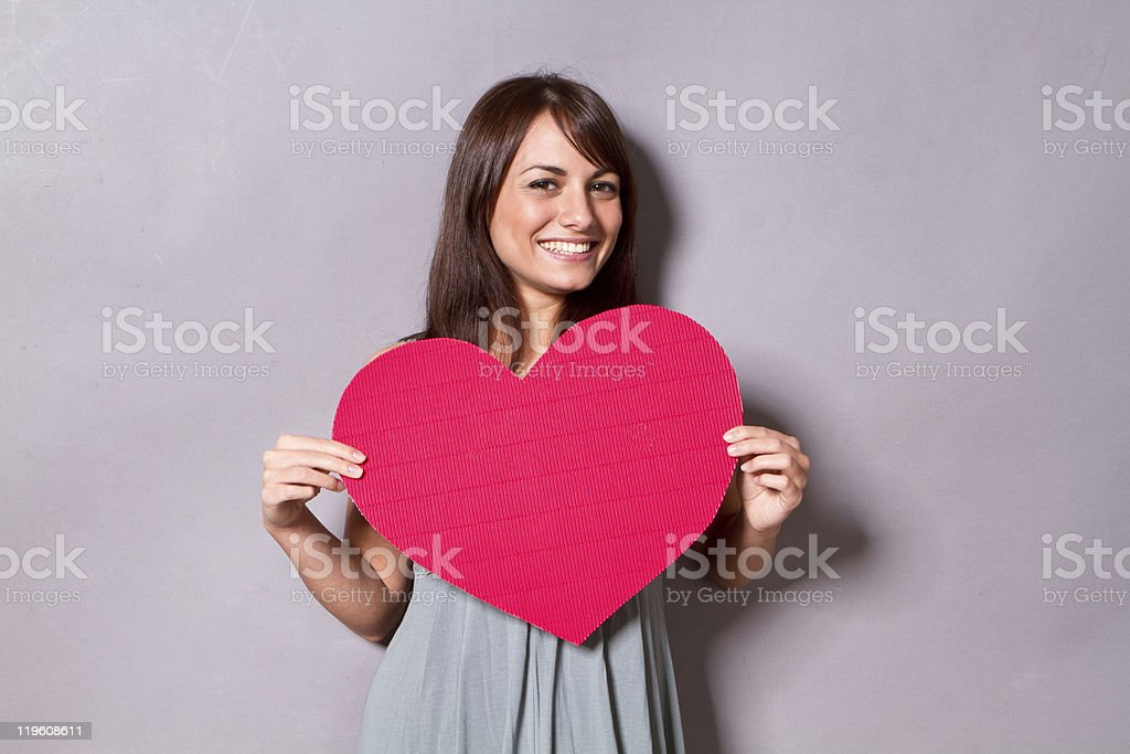 Young woman holds a big red paper heart stock photo