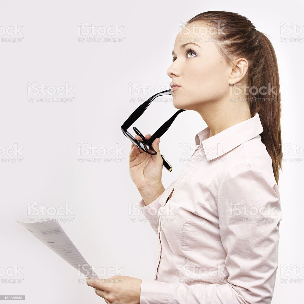 Young woman holds  her spectacles and looking away royalty-free stock photo