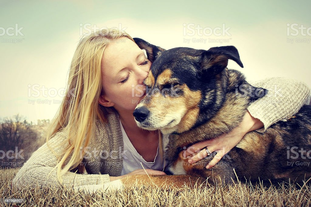 Woman Tenderly Hugging and Kissing Pet Dog stock photo