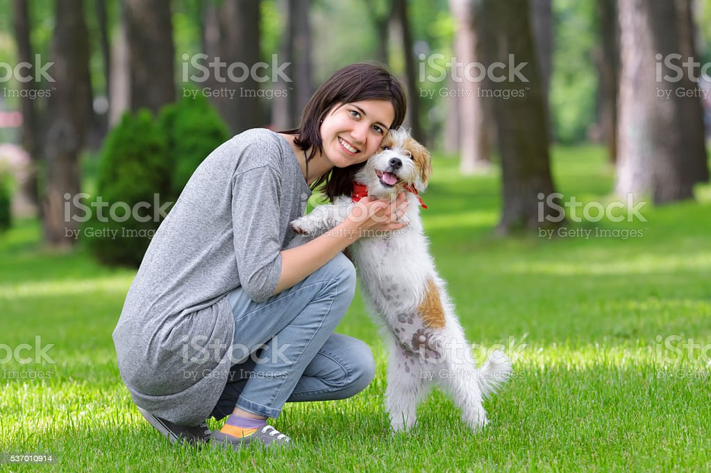 Young woman hugging her dog in summer park stock photo