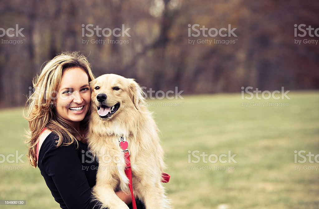 Young woman hugging her dog outside stock photo