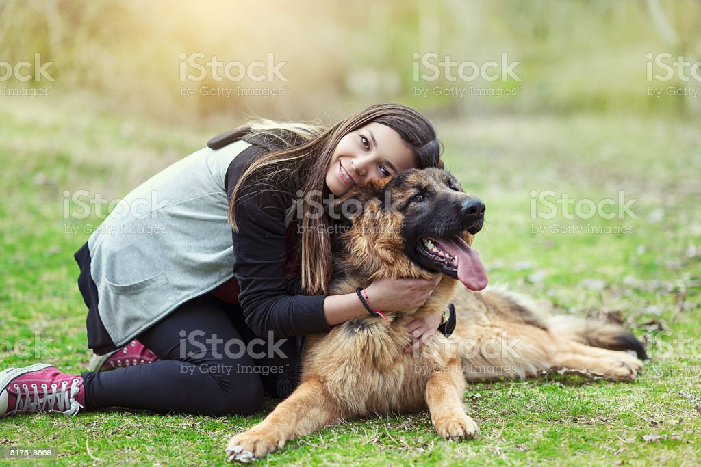 Young Woman Hugging her German Shepherd in the Park stock photo
