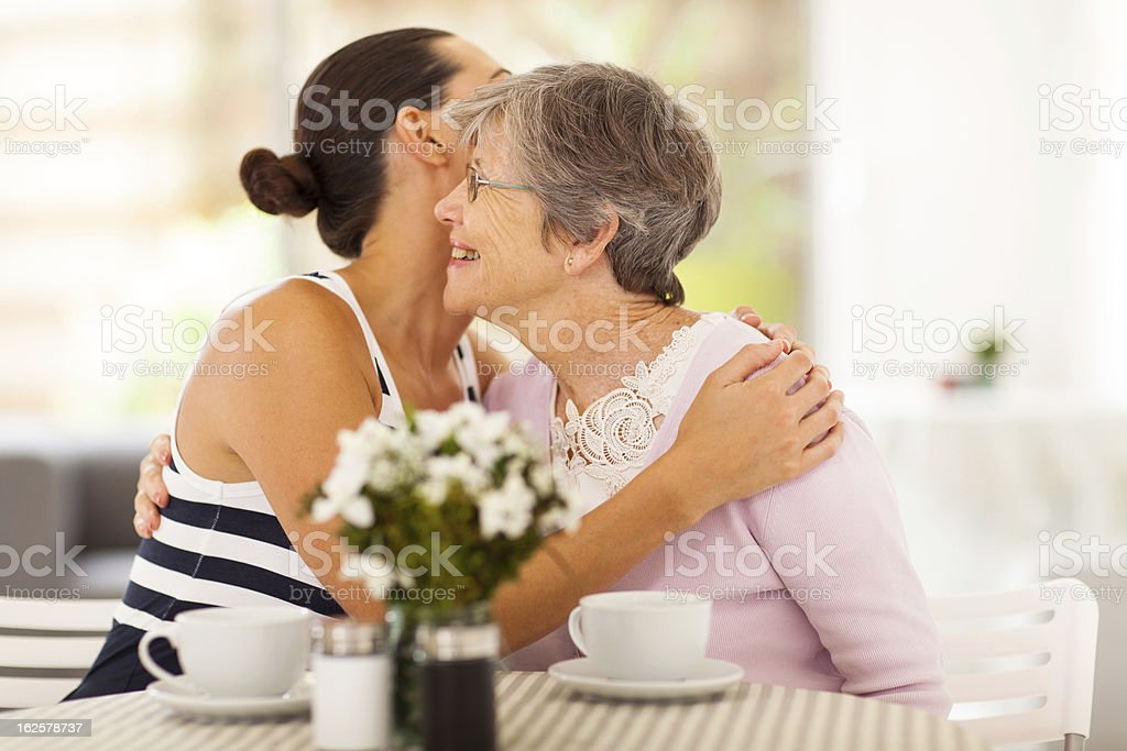 young woman hugging senior mother royalty-free stock photo