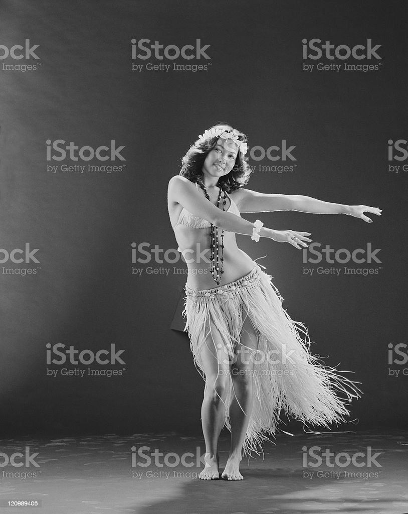 Young woman hula dancer dancing on black background, portrait, smiling stock photo