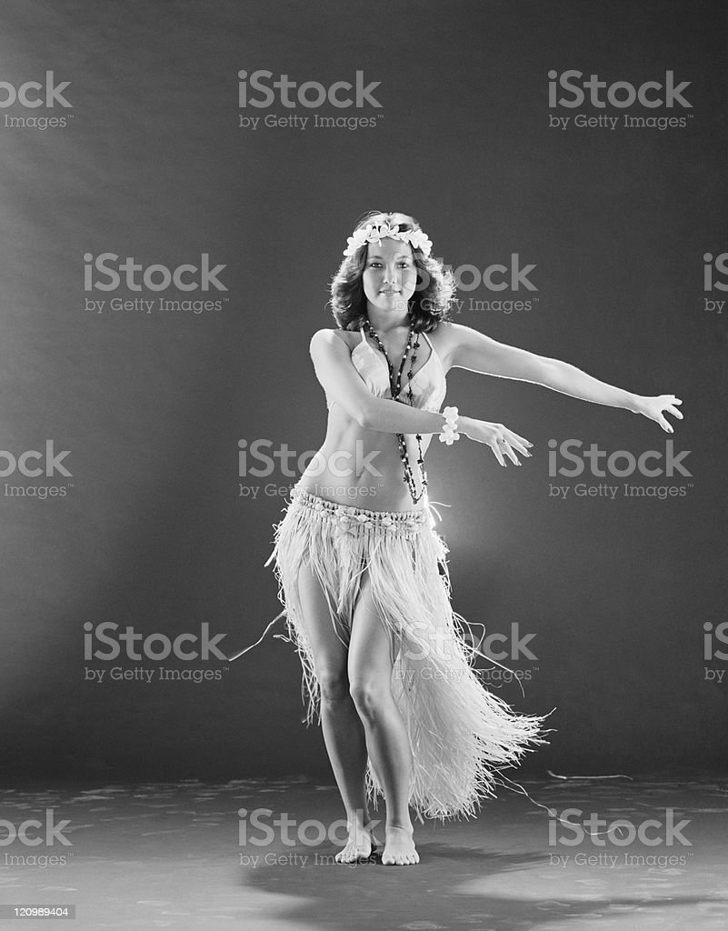 Young woman hula dancer in traditional clothing dancing on black background, smiling, portrait stock photo