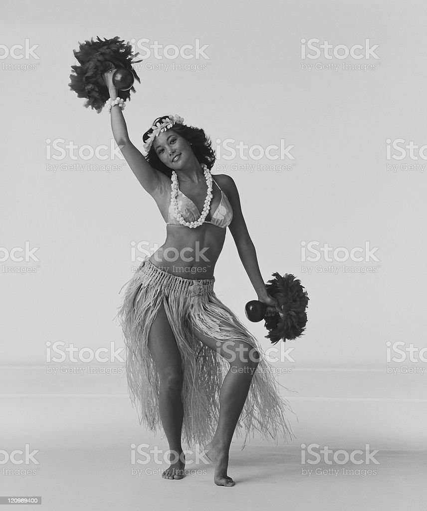Young woman hula dancer with feathered gourd rattle and dancing on white background, smiling, portrait royalty-free stock photo
