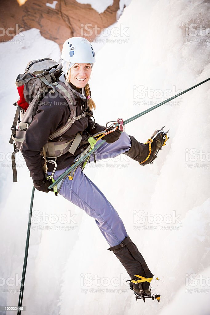 Young Woman Ice Climbing stock photo