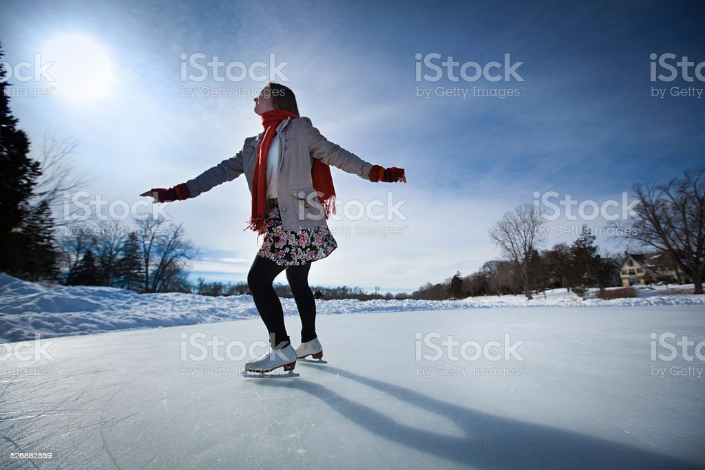 Young Woman Ice Skater Skating on Outdoor Ice Rink stock photo