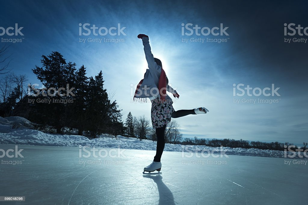 Young Woman Ice Skater Skating on Outdoor Winter Ice Rink stock photo