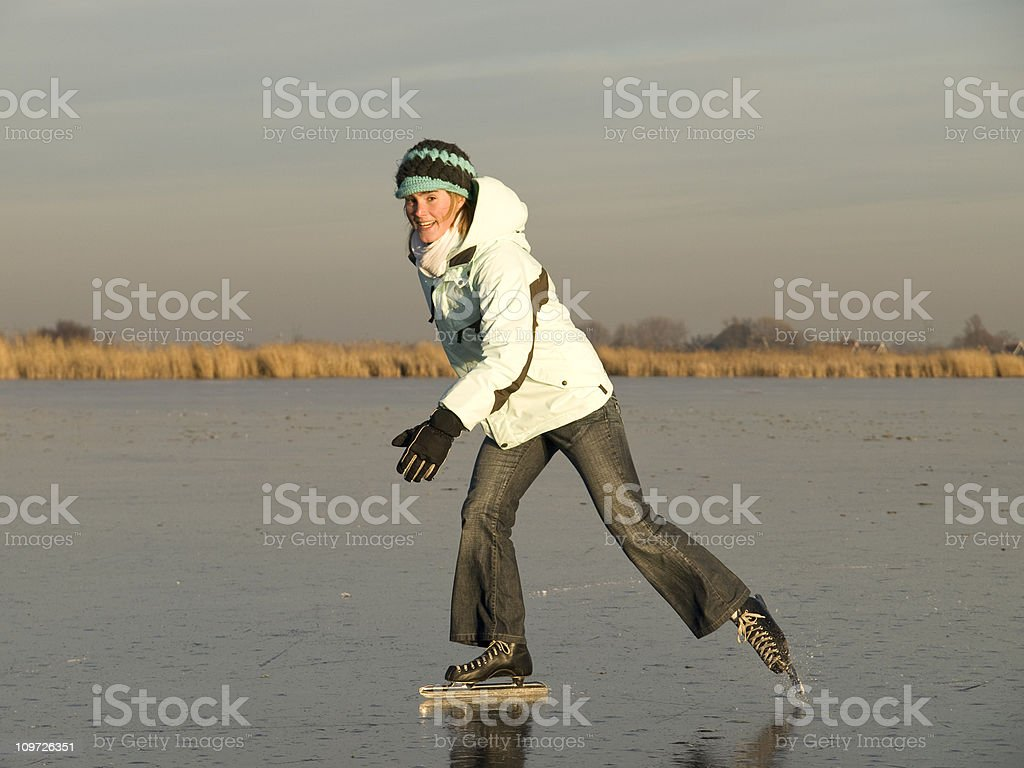 Young Woman Ice Skating on Pond in Field royalty-free stock photo
