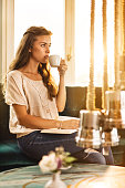 Young woman in a cafe relaxing with cup of coffee.