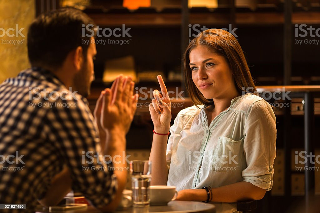 Young woman in a cafe scolding her boyfriend. stock photo
