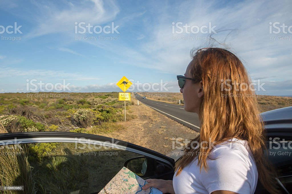 Young woman in a car on roadside reads road map stock photo