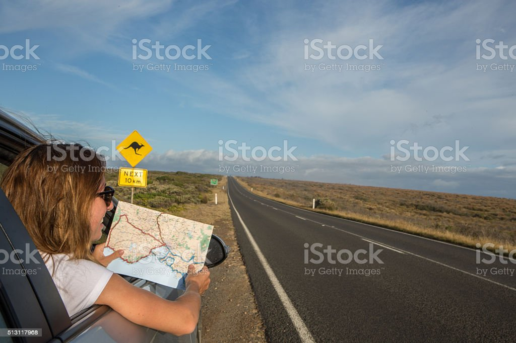 Young woman in a car reads a road map-Australia stock photo