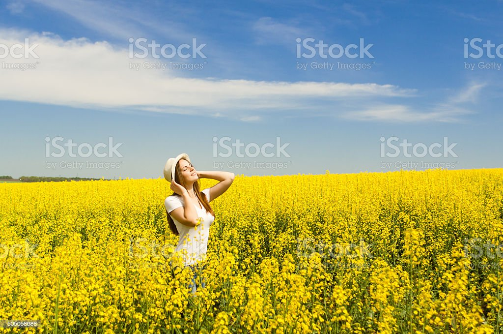 Young woman in a colza field enjoying life stock photo