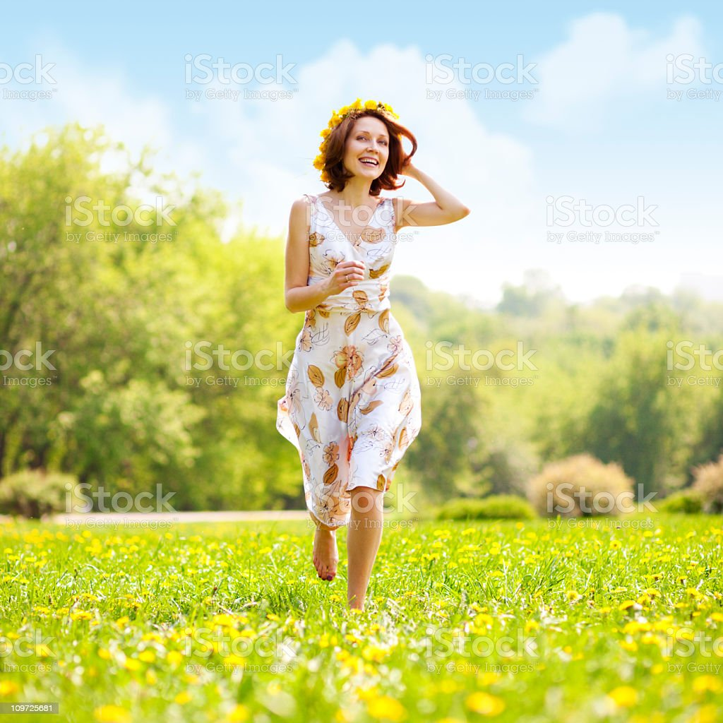 A young woman in a dress running through the grass field royalty-free stock photo