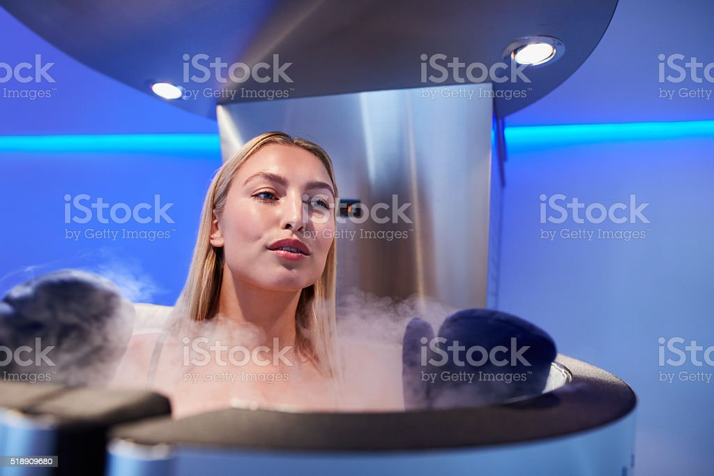 Young woman in a full body cryotherapy cabinet stock photo