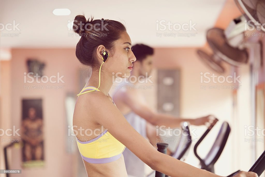 Young woman in a gym on a running treadmill stock photo