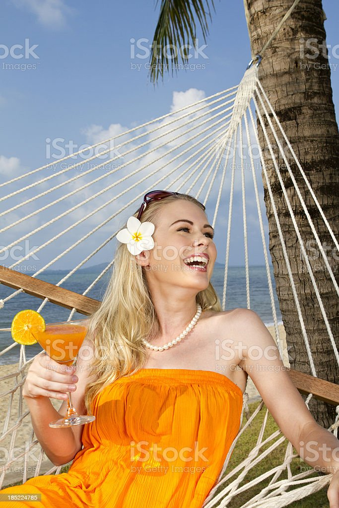 Young woman in a hammock and cocktail on the beach royalty-free stock photo
