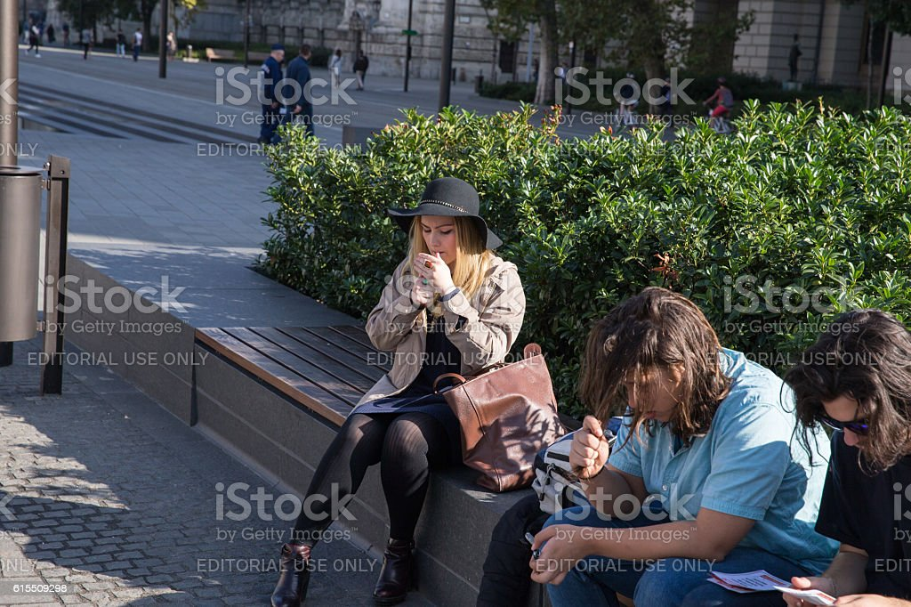 Young woman in a hat smokes, sitting on  bench stock photo