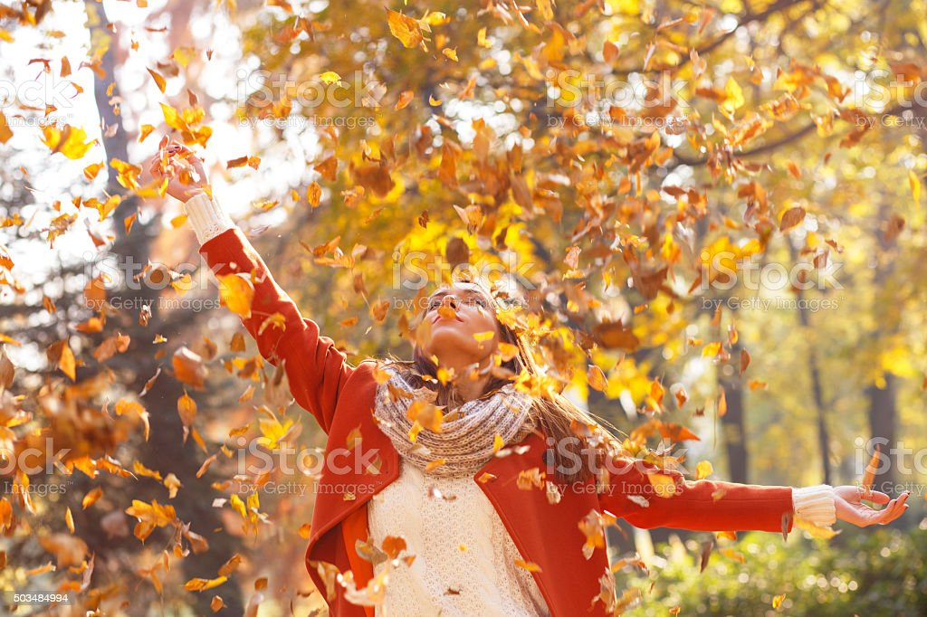 Young woman in a park with arms outstretched stock photo